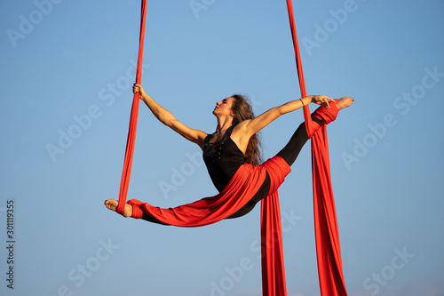 Beautiful and flexible female circus artist dancing with aerial silk on a sky ba Tablou Canvas