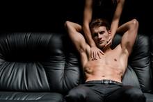 Passionate Woman Hugging Shirtless Man On Sofa In Dark Room