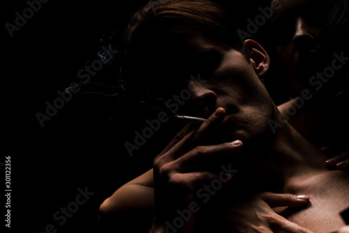 Photo  woman hugging sexy man smoking cigarette, isolated on black