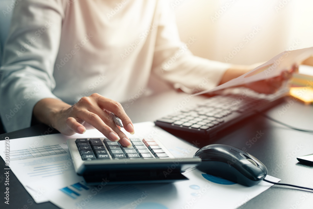 Fototapeta Woman accountant or banker use calculator and computer on table at office