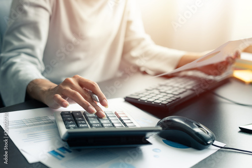 Photo Woman accountant or banker use calculator and computer on table at office