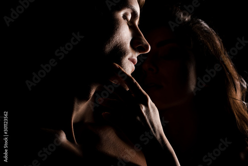 Photo beautiful sexy couple hugging, isolated on black with backlight
