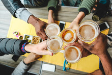 Group Of Friends Enjoying A Beer Glasses In English Pub Restaurant - Young People Cheering At Vintage Bar - Friendship, Happy Hour And Party Concept - Main Focus On Right Half Pint Glass