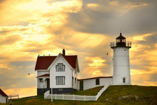 The Lighthouse And The House Of The Keeper Of The Lighthouse On The Hill Against The Sunset Sky. Atlantic Ocean. USA. Maine.  Nubble York