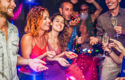 Obraz Happy friends making party throwing confetti, dancing and drinking champagne with dj mixing music - Entertainment, fun, new year's eve, nightlife, concept - Focus on blond man hand - fototapety do salonu
