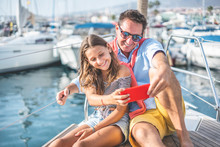 Happy Father And Daughter Taking A Selfie On Sailboat During Ocean Trip Vacation - Family People Having Fun With New Trends Technology - Travel, Tech And Love Concept - Main Focus On Man Face