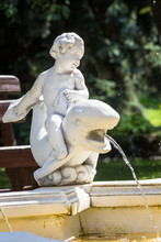 Fountain Element With A Sculpture Of A Child Sitting On A Dolphin