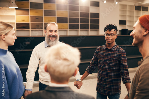 Multiethnic group of people standing in circle holding hands and doing relaxation exercise during therapy lesson