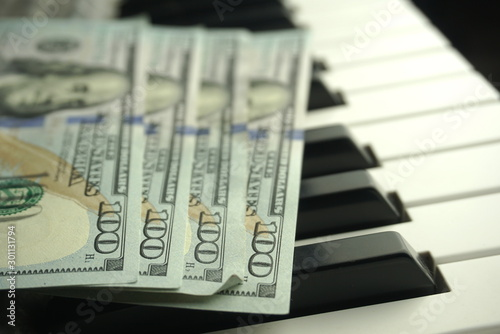 Fotografía one hundred dollars on a piano keyboard close up