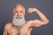canvas print picture - I'm superman. Photo of aged retired handsome man neat long beard showing strong naked shirtless shoulders raise fists strong biceps looking mirror isolated grey background