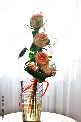 Three beautiful colorful roses with ribbon in glass vase on small table in front of window