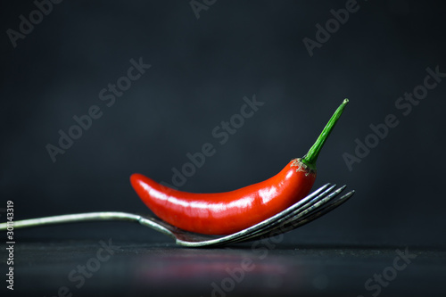 Foto auf Gartenposter Hot Chili Peppers Red hot chili pepper on vintage silver fork on black background.