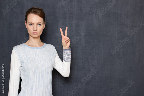 Fotografía  Portrait of serious focused young woman showing peace gesture