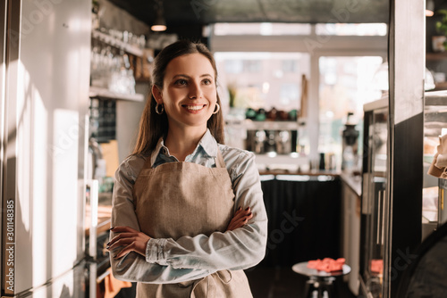 Photo smiling barista in apron standing in sunny cafe with crossed arms