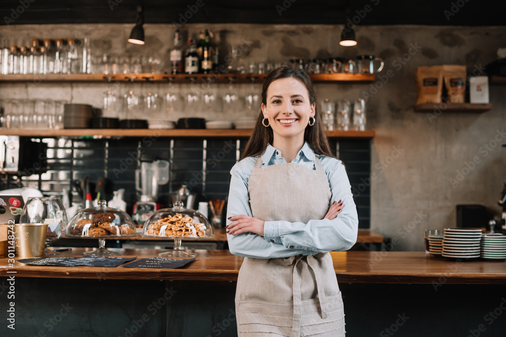 Fototapeta smiling barista in apron standing with crossed arms near bar counter