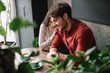 canvas print picture - selective focus of green leaves and smiling romantic young couple hugging and drinking coffee in coffee shop