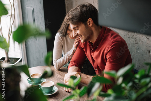 selective focus of green leaves and smiling romantic young couple hugging and drinking coffee in coffee shop