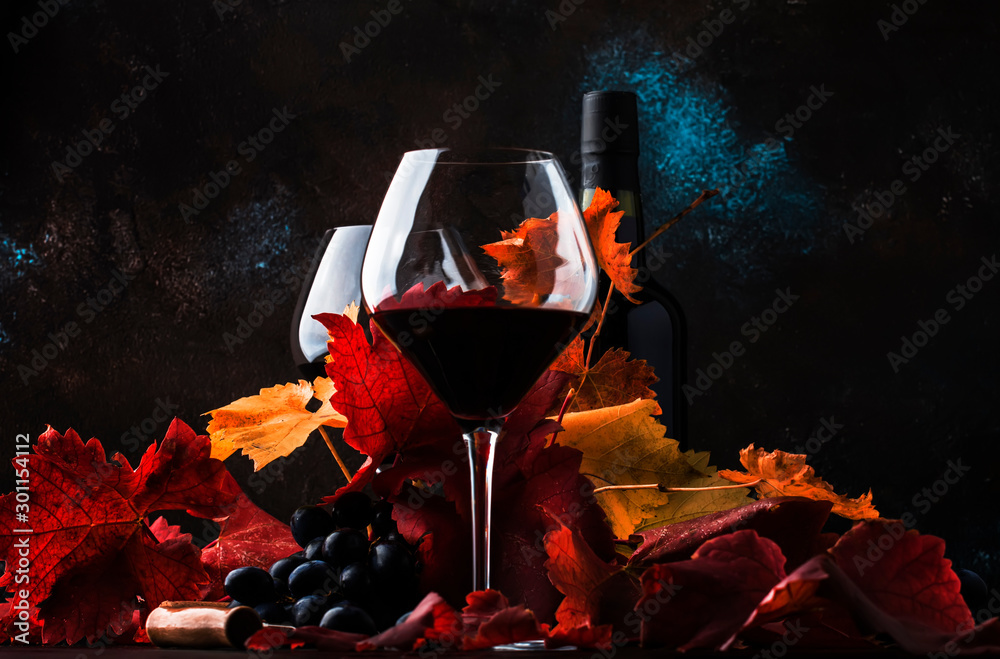 Fototapeta Dry Red Wine in big wine glass, autumn still life with leaves, wine tasting concept, rustic style, selective focus