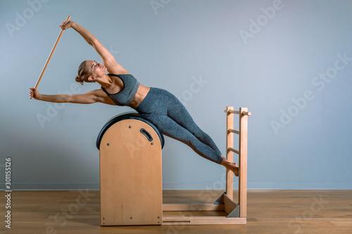 Beautiful woman doing pilates exercise, training on barrels Wallpaper Mural