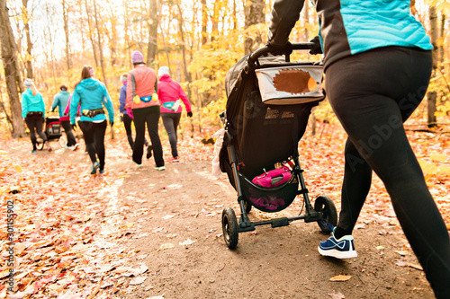 plakat Stroller woman group out running together in an autumn park they run a race or train in a healthy outdoors lifestyle concept