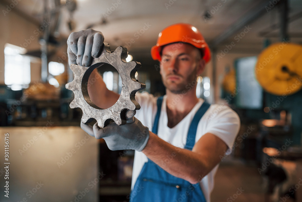 Fototapety, obrazy: Part of engine. Man in uniform works on the production. Industrial modern technology
