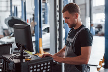 Professional Mechanic. Man At The Workshop In Uniform Use Computer For His Job For Fixing Broken Car