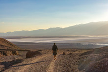 Lone Hiker In Shorts Walking On A Dusty Gravel Trail Holding A Water Bottle In The Desolated Desert Landscape Of Death Valley, California, US. Mountains And A Dried Up Lake At The Background