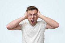 Man In Glasses Screaming And Covering His Ears Because He Can Not Stand The Noise.