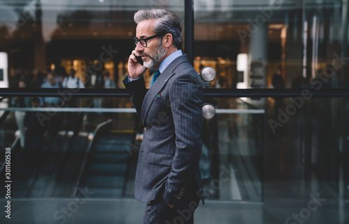 Pinturas sobre lienzo  Businessman talking on phone standing near glass wall