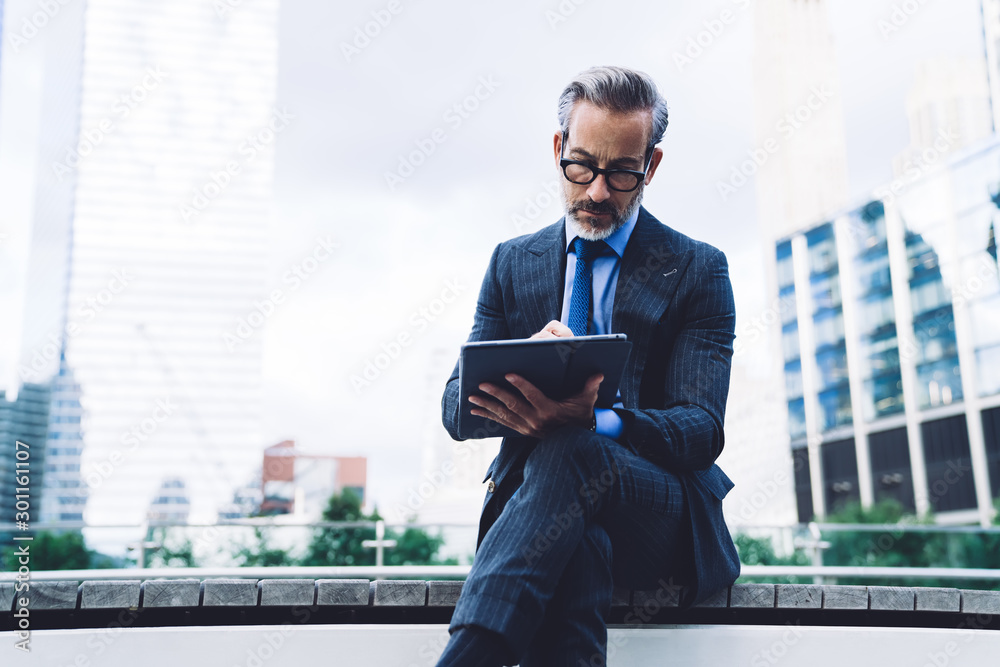 Fototapeta Mature male in business suit using tablet with stylus
