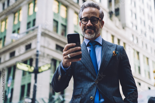 Fotomural  Smiling businessman with phone in hand