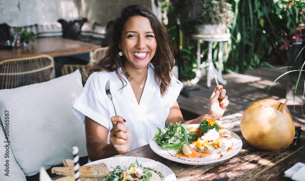 Fototapeta Excited ethnic woman dining at exotic cafe