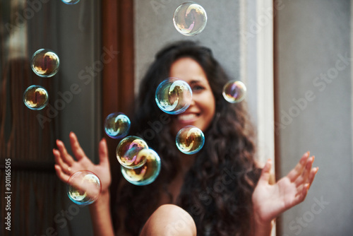 Obraz Cute girl plays with bubbles like a child. Beautiful woman with curly black hair have good time in the city at daytime - fototapety do salonu