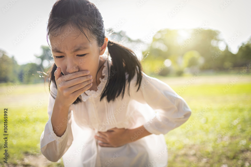 Valokuva Asian beautiful child girl covered her mouth about to throw up,vomit,puke retch