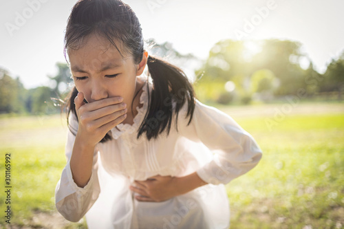 Asian beautiful child girl covered her mouth about to throw up,vomit,puke retch Fototapeta
