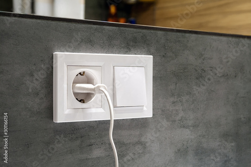Foto A closeup diagonal view of a group of white european electrical outlet with a pl