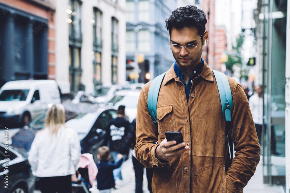 Fototapety, obrazy: Hispanic young man in eyeglasses typing on smartphone on street