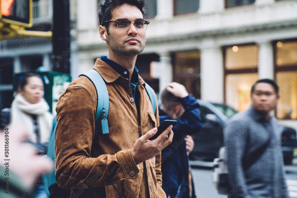 Fototapety, obrazy: Thoughtful Hispanic young man standing on busy sidewalk with smartphone