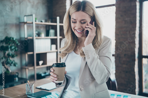 Obraz Photo of beautiful blond business lady chief holding telephone speaking with aged retired mom little corporate break drink hot coffee to-go formalwear blazer modern office - fototapety do salonu