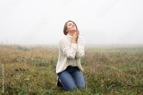 Obraz na plátne Girl closed her eyes on the knees, praying in a field during beautiful fog