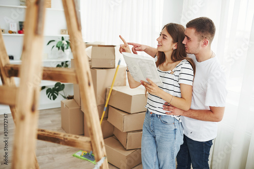 Obraz Cheerful young couple in their new apartment. Conception of moving - fototapety do salonu