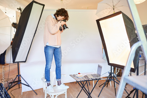Obraz Photographer on a chair is photographing food - fototapety do salonu