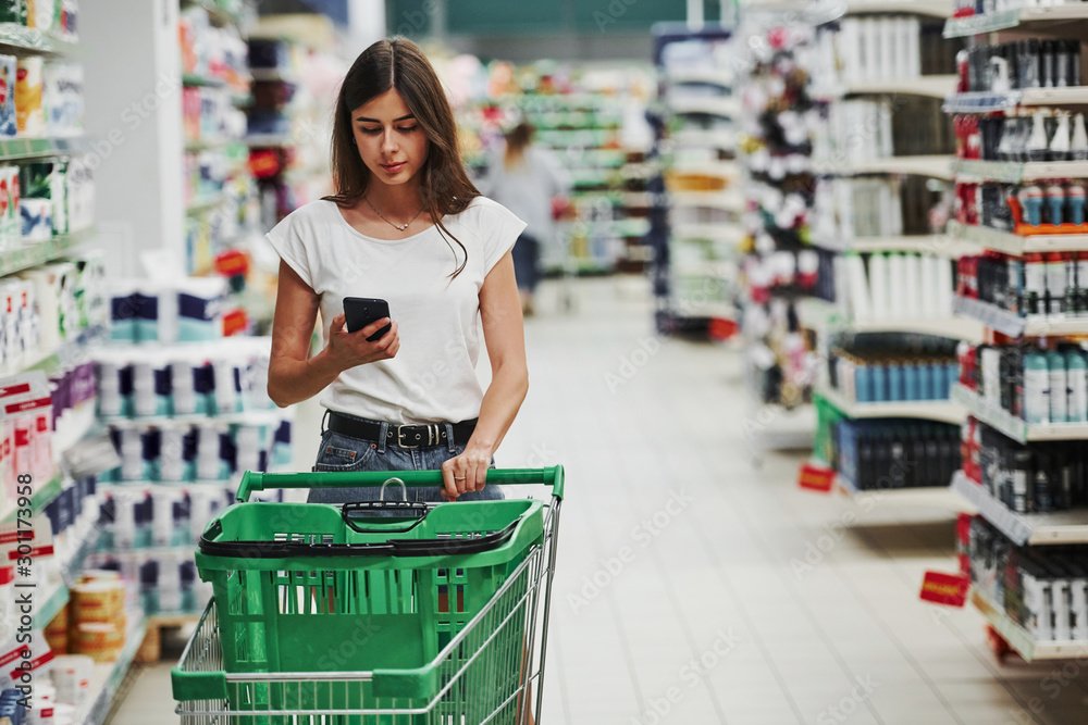 Fototapeta Using smartphone. Female shopper in casual clothes in market looking for products