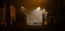 Lonely Woman Walking In Foggy Old City With Street Lights In A Coat