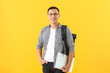 Male Asian student with laptop on color background