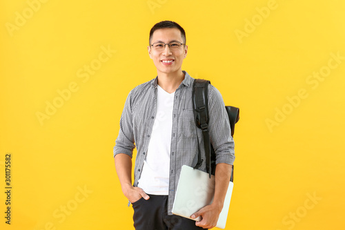 Fotografía  Male Asian student with laptop on color background