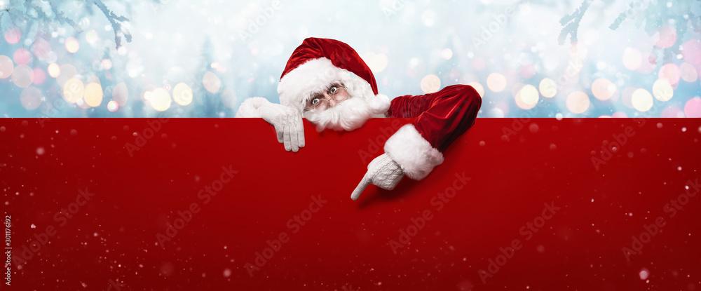 Fototapeta Santa Claus Showing Something On a Red Wall
