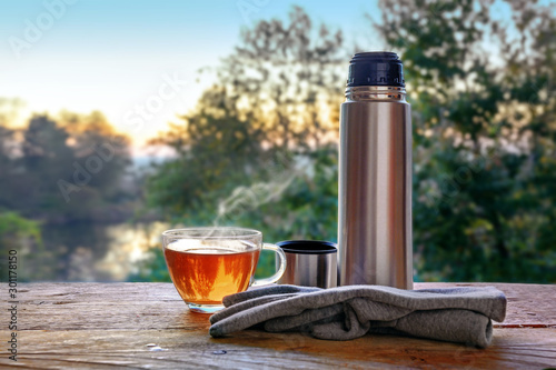 Foto auf Leinwand Tee Break with hot tea at a trip in the nature, glass cup, thermos jug and gloves on a rustic wooden table in front of a blurred landscape, copy space