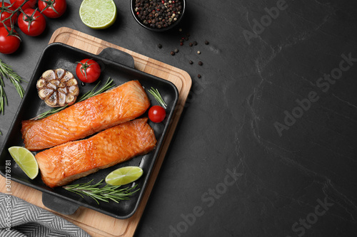 Delicious roasted fish served on black table, flat lay. Space for text
