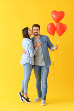 Portrait Of Beautiful Young Couple With Air Balloons On Color Background